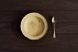 enamelled plate and spoon on wooden table