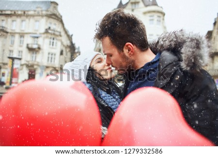 enamored couple in winter clothes is kissing outdoors with a heart shaped red balloons on foreground. enamored man and woman having fun together at winter day #1279332586