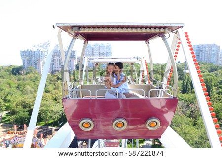 Enamored couple of beautiful people, boy and girl kissing, hugging, posing for photo, ride on ferris wheel, smiling, laughing and sit in booth ferris wheel on background of city, sky and trees at an #587221874