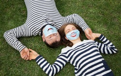 enamored man and woman in striped sweaters lie on the grass, holding hands. Both wear blue medical masks with funny smiles painted on them. Positive, romance in quarantine, covid- 19 pandemic