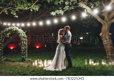 Enamored newlyweds gently embrace. Wedding ceremony in nature. The lights of the electric garland illuminate the wedding party. #783225343