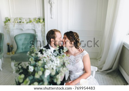 Enamored newlyweds in a beautiful white interior are sitting at a white round table. Enamored newlyweds are smiling cheerfully. #769954483