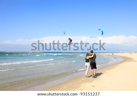 Enamored young couple hagging each other and going by Mediterranean coast on the  background of kite-surfers in air - stock photo