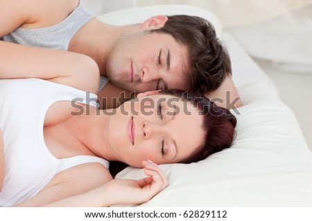 Enamored young couple sleeping in bed together in the bedroom