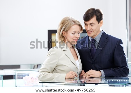 Enamoured couple of middle age in jeweller shop