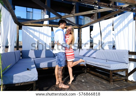 Enamoured guy and girl, bride and groom looking into each others eyes, smiling and embracing, posing on camera and standing in bungalow with white curtains on pier on background of hotel outdoors #576866818