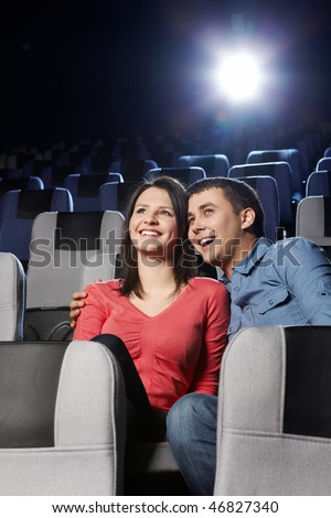 Enamoured laughing couple at a cinema on a forward background
