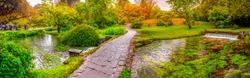 enchanted eden garden path bridge trail over pond in horizontal panoramic garden .