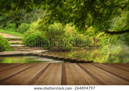 Enchanted forest scene of slow flowing stream with vibrant reflections with wooden planks floor