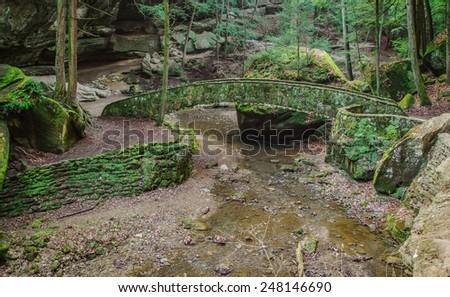 Enchanted Forest. Stone bridge encased in moss crosses a stream. Hocking Hills State Park. Logan, Ohio.