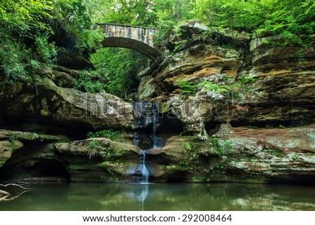 Enchanted Forest Waterfall. Stone bridge crosses over an enchanting forest waterfall. Hocking Hills State Park. Logan, Ohio.