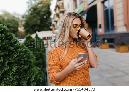 Enchanting blonde young woman waiting for phone message while drinking coffee on the street. Stylish girl in yellow sweater posing on alley holding smartphone and enjoying cappuccino.