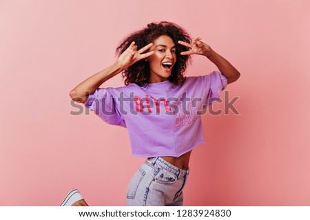 Enchanting brunette girl funny posing with peace sign. Studio photo of blithesome woman isolated on rosy background.