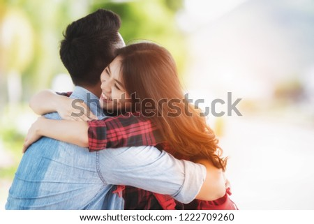 Encounter of  Asian Young Couple happy hugging in love on street after arrival in summer with a warm sunlight background.