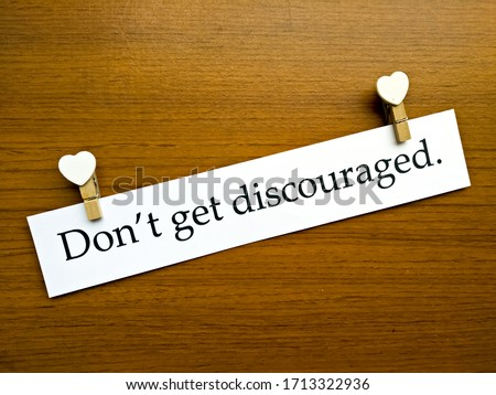 Encouragement Concept, The sentence 'Don't get discouraged.' in a white paper with white heart shapes and wooden pattern background. Stock photo ©