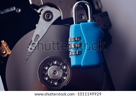 Encrypted hard disk. Padlock with cipher on an opened hard disk. Data loss