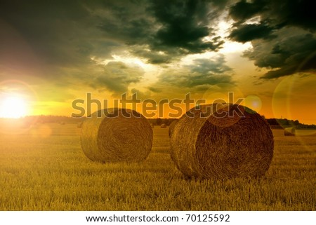 End of day over field with hay bale