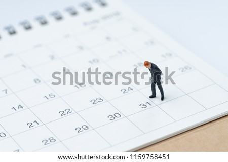 End of month for salary man concept, miniature people businessman office guy standing and looking at number 31 date, waiting to get money and pay day.