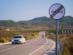 End of the ban on overtaking. A white round sign on a country road allows overtaking. A white car comes towards. In the background are mountains.