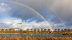 End of the rainbow over a lake in a winter afternoon before a heavy rain shower
