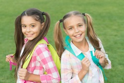 Ending of school year. Cheerful smart schoolgirls. Happy schoolgirls outdoors. Small schoolgirls with backpacks. September. Vacation is over. Back to school. Cute schoolgirls with long ponytails