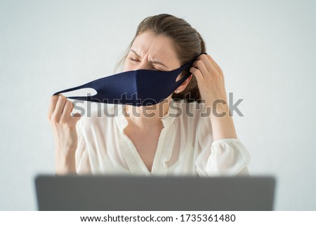 Ending quarantine. Young woman works in an office at a laptop, tired of quarantine measures, annoyed, takes off a medical mask on a white background