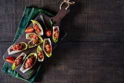 Endive salad boats filled with pico de gallo over minced beef served on a rustic cutting board on a dark wooden background, horizontal orientation, top view, copy space