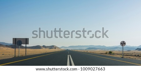 Endless desert road with clear sky