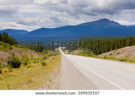 Endless empty road of Alaska Highway, Alcan, crossing wide open expanse boreal forest taiga landscape west of Watson Lake, Yukon Territory, Canada