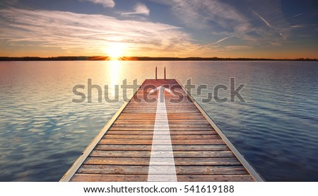 endless jetty with an arrow leading over lake to the horizon. Concept for proceeding to success.                                 #541619188