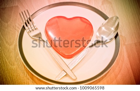 Endless love Valentine's day concept, Top view of red heart placed on plate with fork, menu in romatic love background. Love is passion for couple that show for serving or delivery of love to somebody