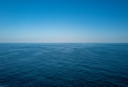 endless ocean with a small lost looking sailing yacht