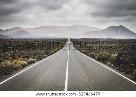Endless road to Timanfaya National park in Lanzarote, Canary Ispands, Spain, Europe, Africa. Volcanic, black sand, harsh, tough, inhospitable, dry, sub-tropical, desert landscape. #529466479