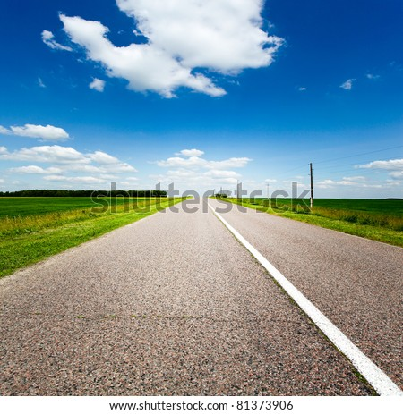 endless rural road and blue cloudy sky