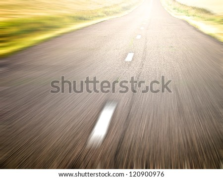 endless rural road in fast and quick traffic motion blur