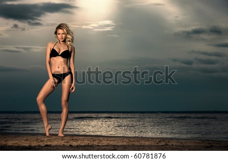 Endless sky. Young woman posing on beach in bikini at sunset with sea in background.