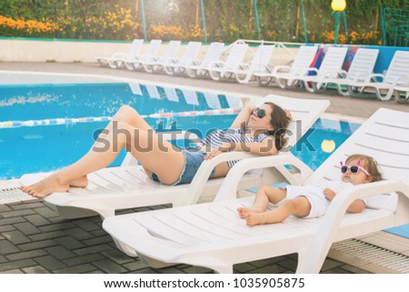 Endless summer. Cute baby and mother relaxing at sunbed near pool at resort. A little girl wearing sunglasses. Child and mom sunbathe. Fashion girls, friends, family at resort #1035905875