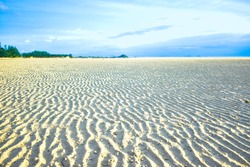 Endless wavy white sand bar at the sea that reveal during low tide. Beautiful wide sand ground under gorgeous blue sky in summer. Coastal landscape and seascape at Nathon Town, Samui Island, Thailand.