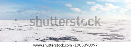 Endless white desert of snowy ice cover on frozen Lake Baikal on a frosty winter day. Tourists on the all-terrain vehicle Hivus travel across the icy expanses. Winter landscape. Natural background Stock photo ©