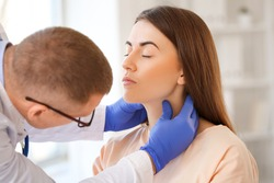 Endocrinologist examining throat of young woman in clinic