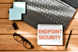 ENDPOINT SECURITY inscription in a notepad near a laptop  and eyeglasses on a wooden background. Business concept. Flat lay.