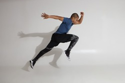 Endurance and stamina. Side view of athletic young Afro American sportsman training in studio, doing high jumps. Action shot of serious determined dark skinned male in sportswear jumping at white wall