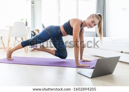 Enduring concentrated sporty woman is doing working out at home and doing plank in front of her laptop, wearing sport outfit