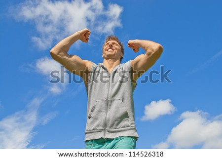 Energetic and happy young man on blue sky background.