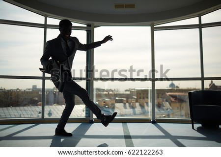 Energetic businessman with briefcase dancing indoors #622122263