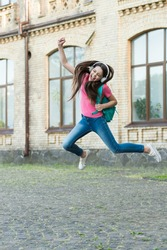 Energetic child girl jumping dancing listening music headphones, real happiness concept.