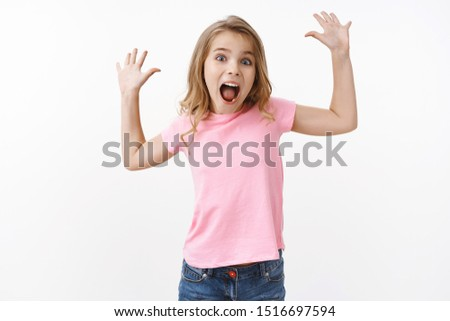 Energetic cute lovely happy kid with blond hair, raise hands up want scare parents screaming joyful, look entertained, having fun playing with school friends, joyfully spend summer holidays in camp