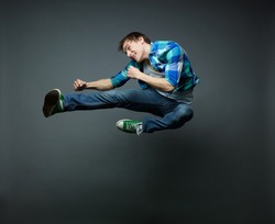 Energetic guy jumping with fists clenched tight and kicking the air