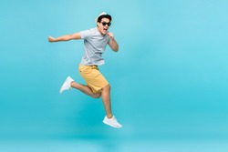 Energetic happy young Asian man jumping studio shot isolated in light blue background
