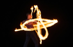 Energetic man performer create sparkling fire patterns twirling burning baton in dark outdoors, pyrotechnics
